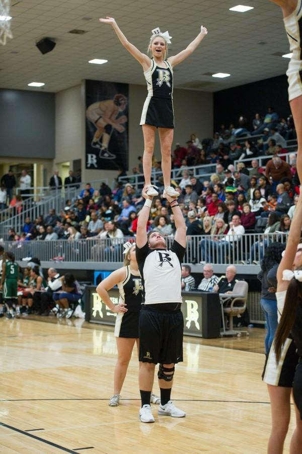 Senior+Andrew+Truman+lifts+sophomore+Kenzie+Schwers+during+a+basketball+game+performance+with+the+cheer+team.+