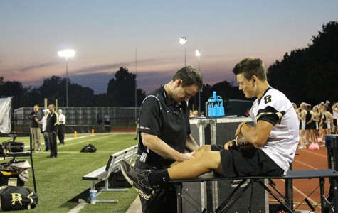Sophomore Tucker Dunlap has his knee looked at by the coaching staff after injuring it on the field.