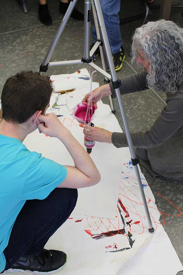 Art teacher Jennifer Deal helps sophomore Nate Brazelton with his pendulum painting project.