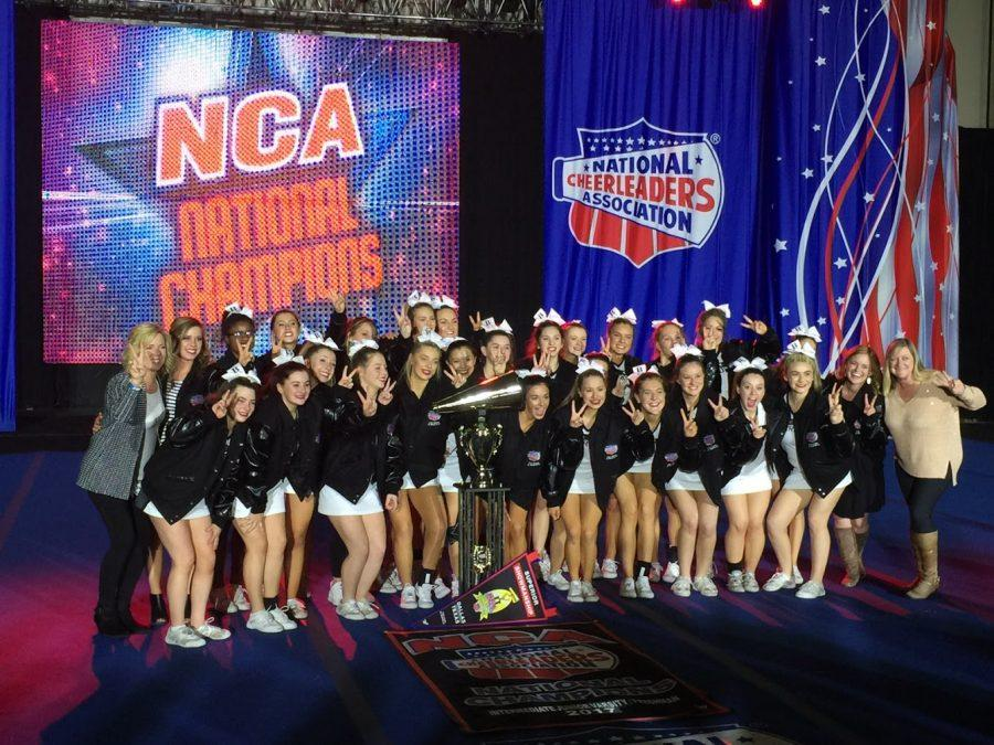 The+JV+Cheer+team+holds+up+two+fingers+to+represent+their+two+NCA+wins.