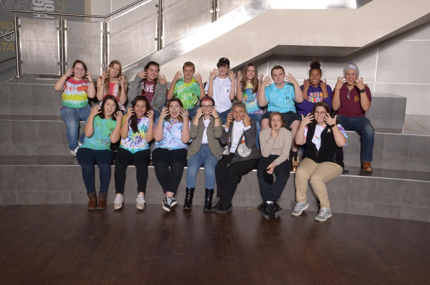 ASL Club demonstrates the sign for Tiger during their group photo.
