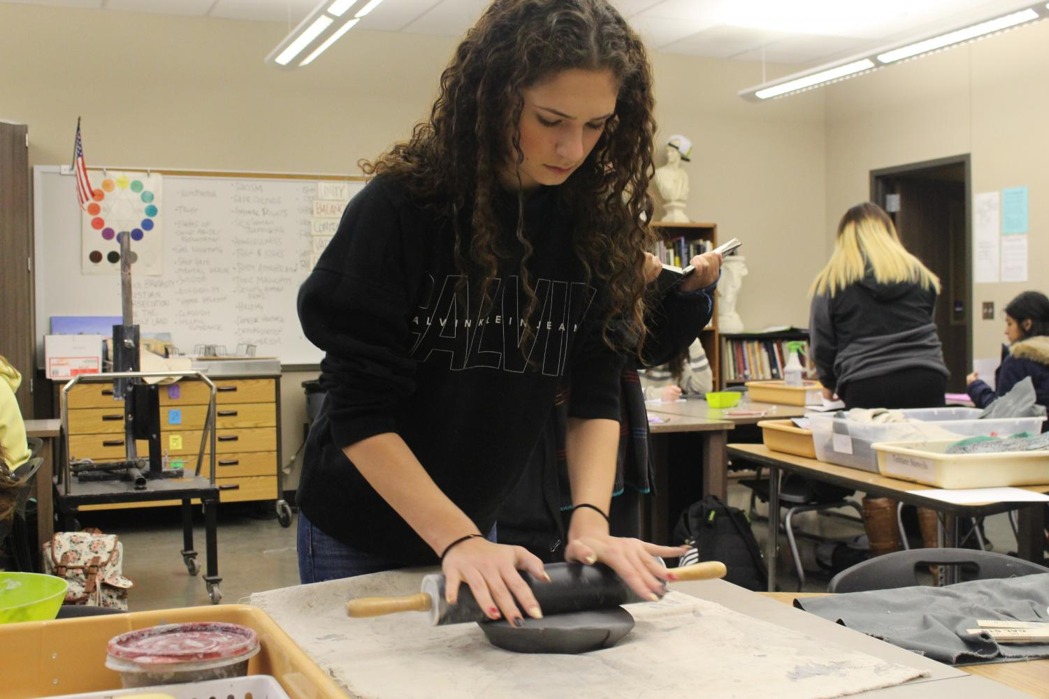 Students work on their bowls and spoons in art class.