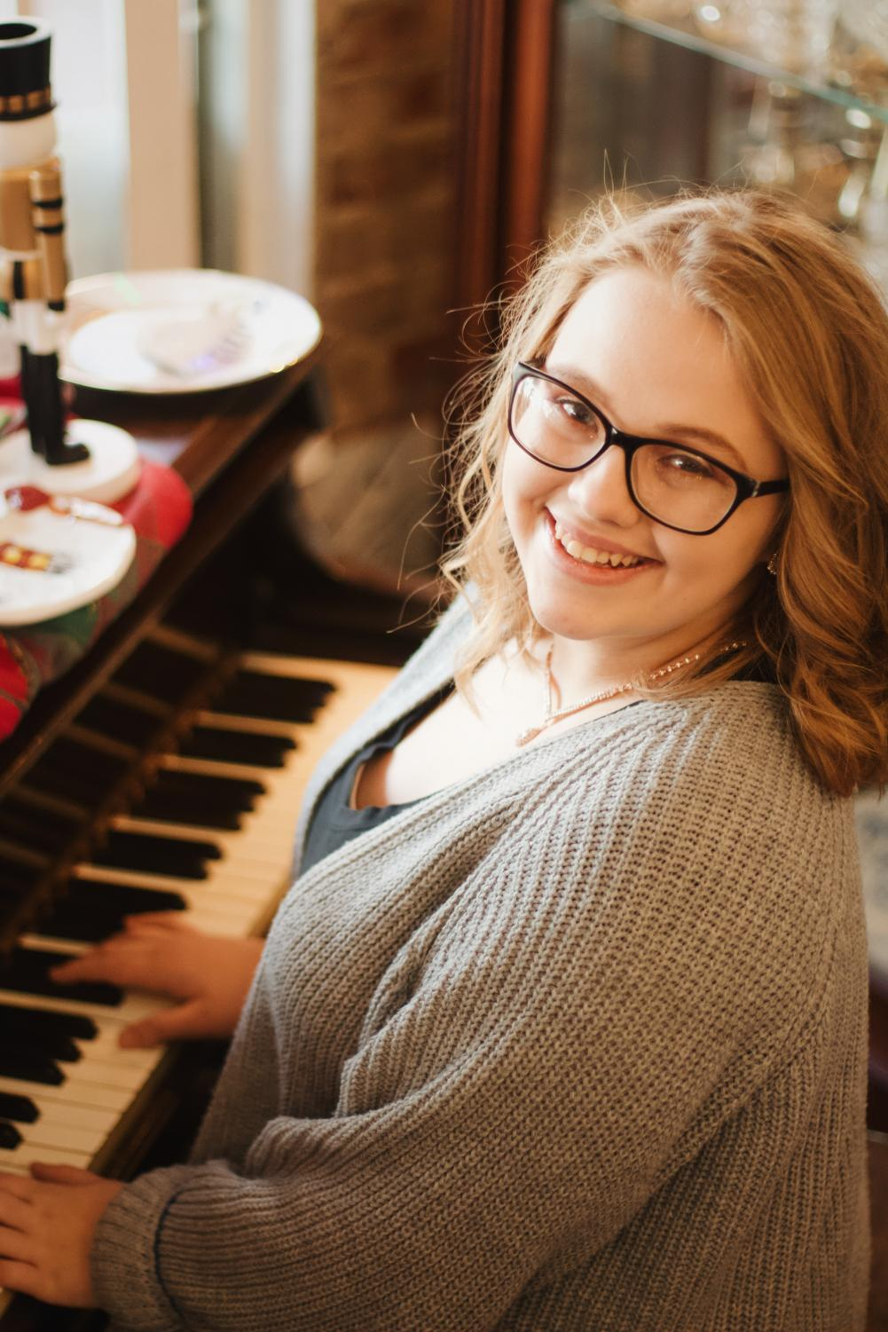 Senior Brittney Schaefer smiles while playing the piano.