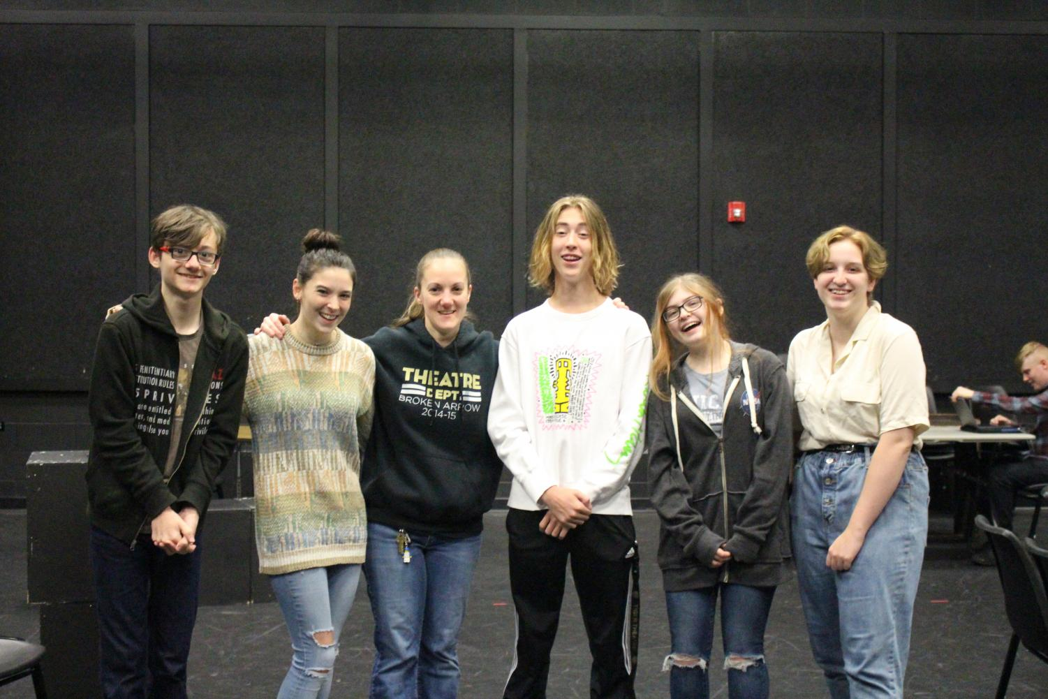 Drama teacher Crystal Krachtt poses with past and current students.