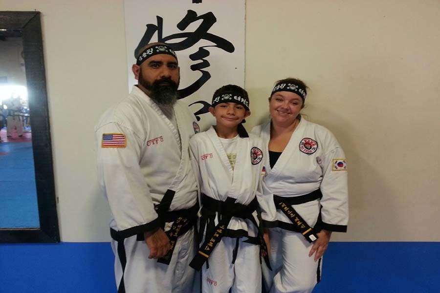 Black belt English teacher Patricia Torres poses for a photo with her husband and son, who both have black belts as well.