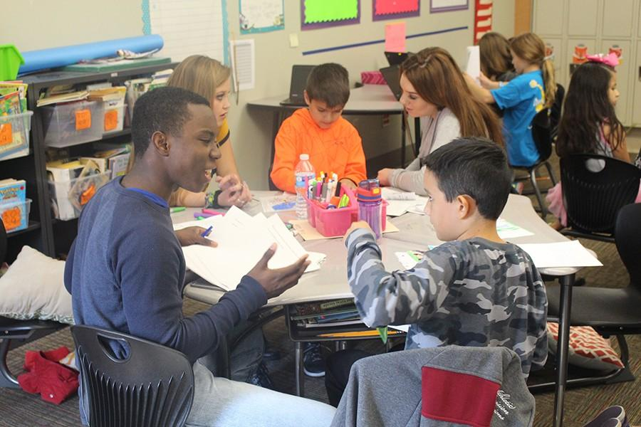 Junior Kam King works with a Creekwood student to produce a children's book.