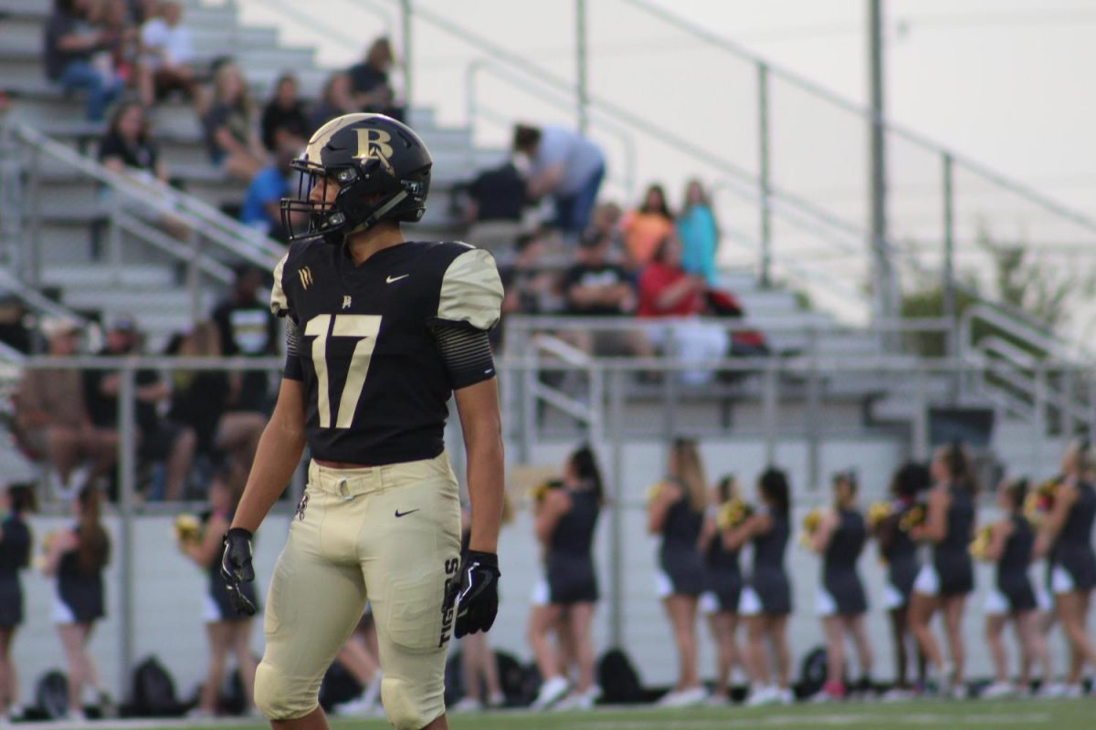 Senior Damian Everette waits for the play on the field. Damian plays both football and basketball and is yet to commit to a plan for next year.