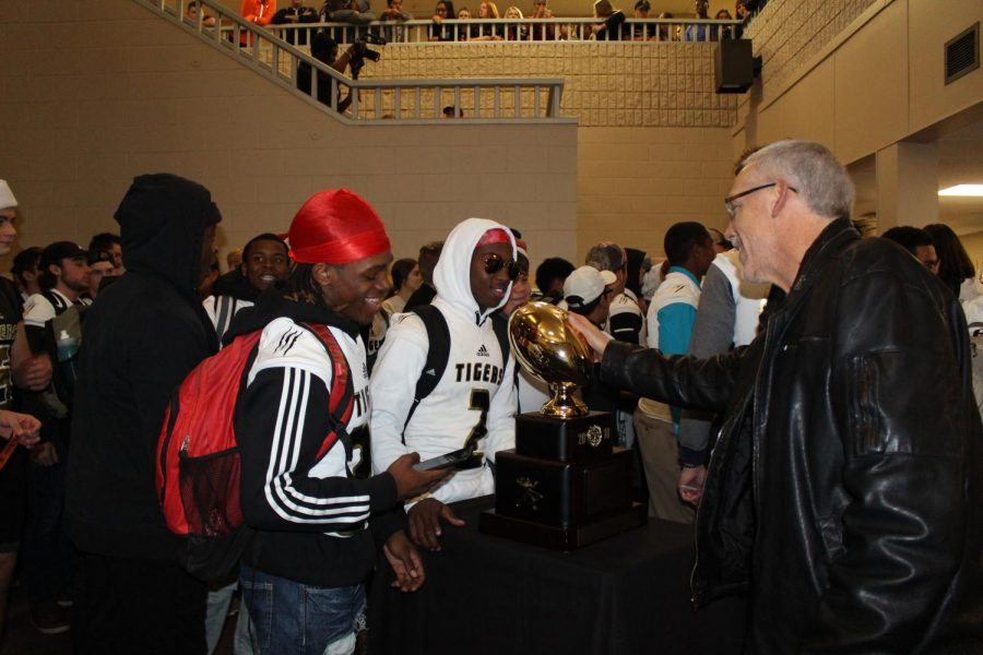 During a mobile pep assembly, football players show off the gold ball.