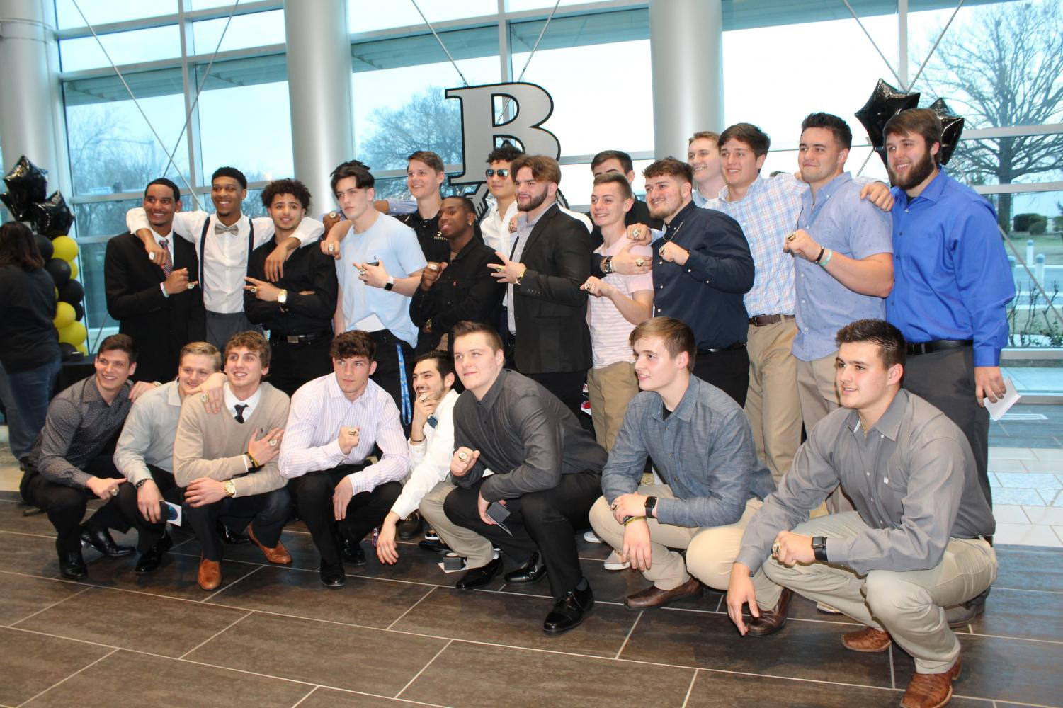 Senior members of the state championship football team pose for a photo after receiving their state rings in a special ceremony.